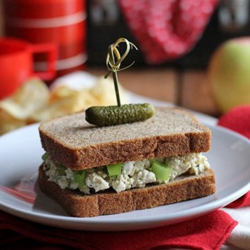 Vegan egg salad sandwich on plate with pickle speared on top.