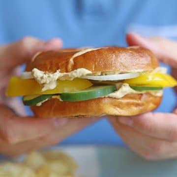Hands holding bagel sandwich.