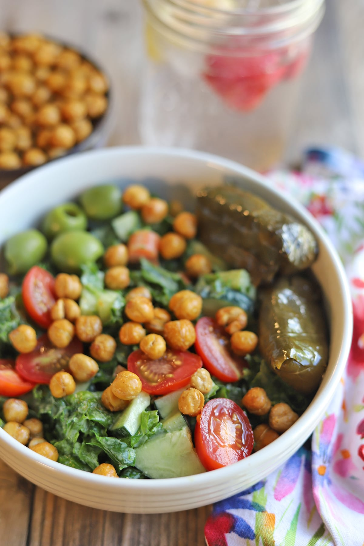 Close up kale salad with dolmas, air fried garbanzo beans, and olives.