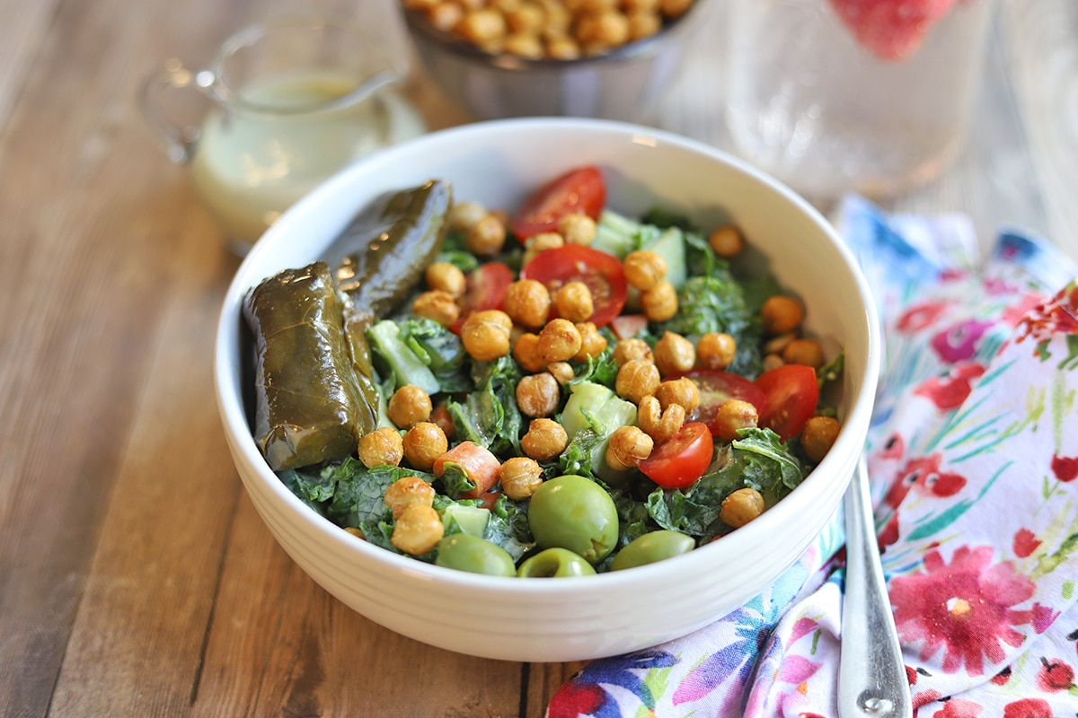 Kale salad in bowl with roasted chickpeas, dolmas, and olives.