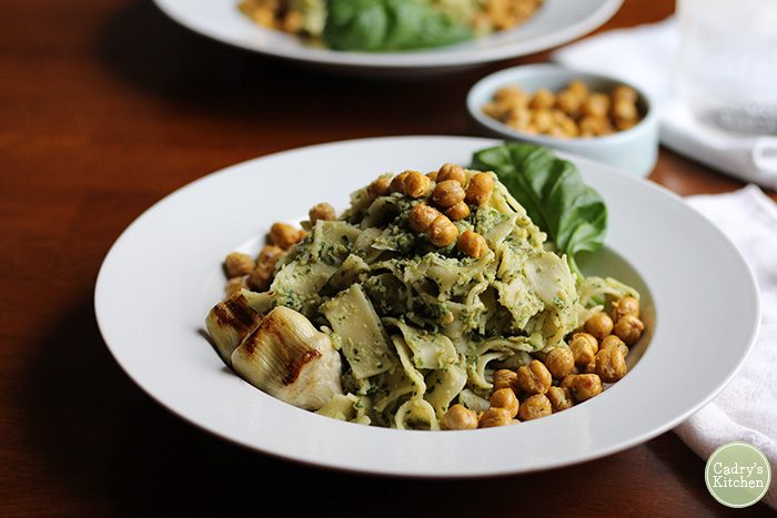 Pappardelle tossed with pesto in bowl with roasted chickpeas.
