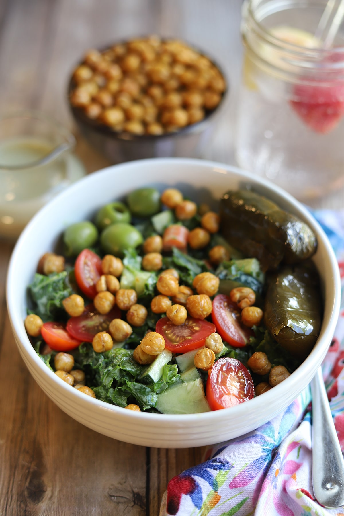 Massaged kale salad in bowl with dolmas and olives.