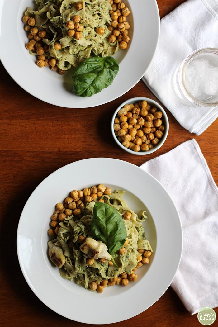 Overhead bowls of pasta with pesto and roasted chickpeas.