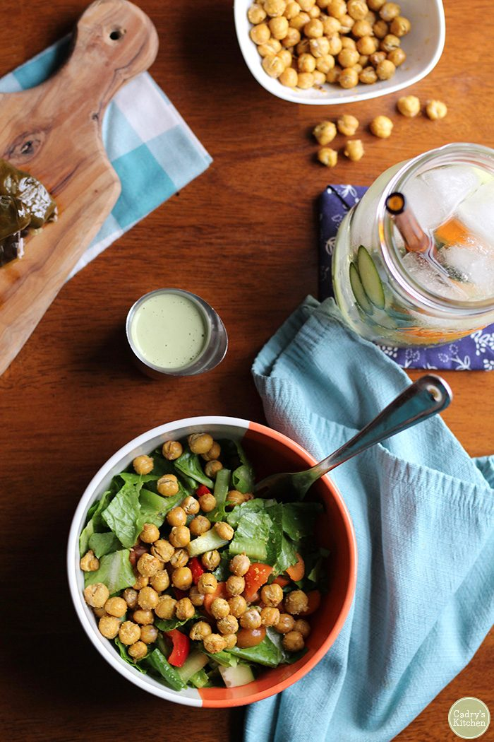 Overhead salad with air fryer chickpeas, water, dressing, and small bowl of air fried chickpeas.