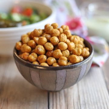 Roasted garbanzo beans in bowl on table.