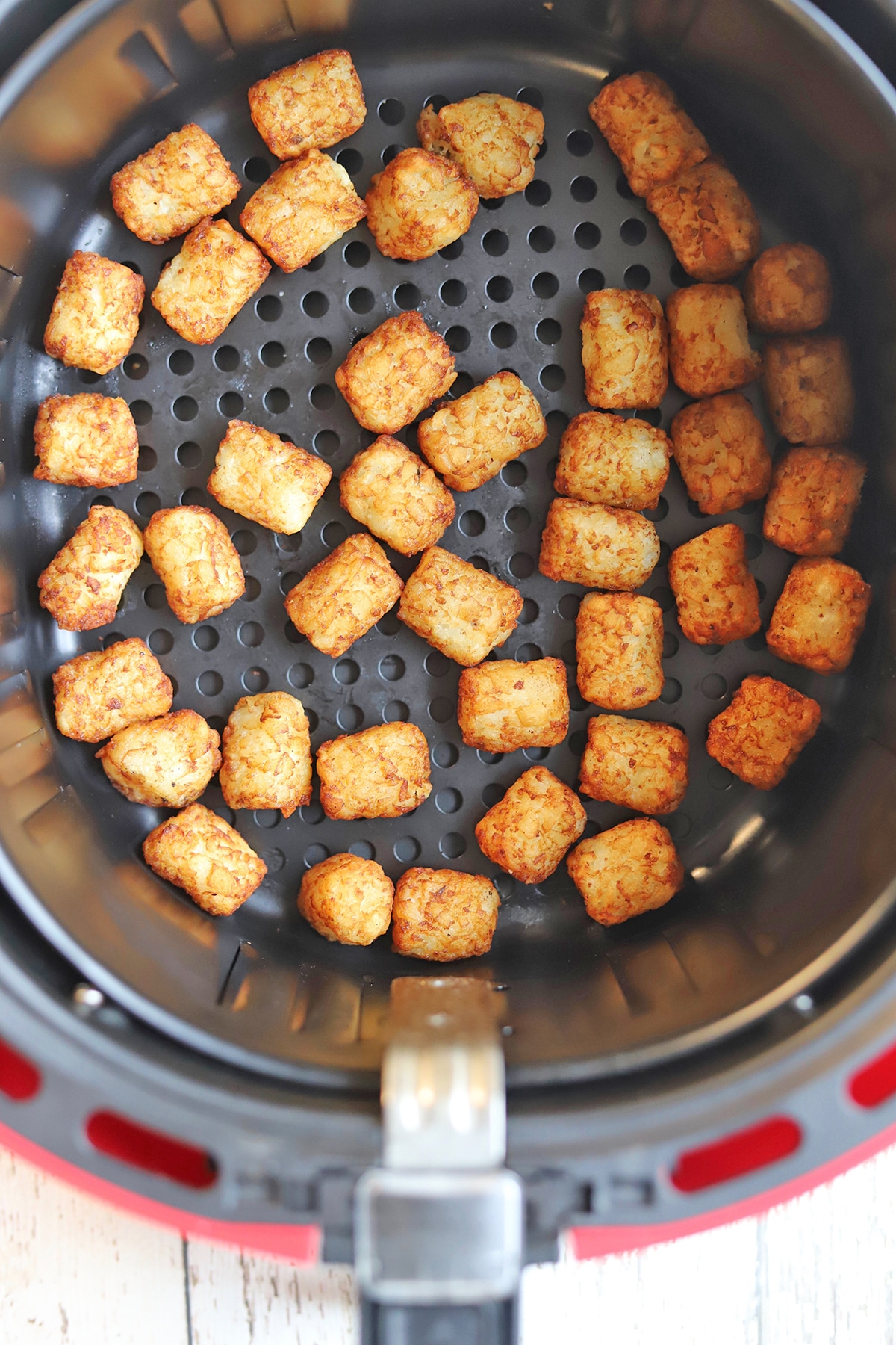 Overhead tater tots in air fryer basket.