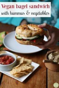 Vegan bagel sandwich with hummus & vegetables written in text. Hand holding bagel sandwich.