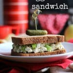 Text: Vegan egg salad sandwich. Sandwich with tofu on bread, speared with pickle on plate.