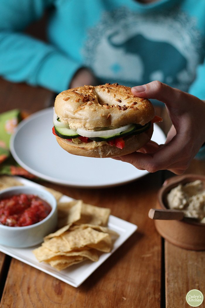 Hand holding bagel sandwich with hummus & vegetables.