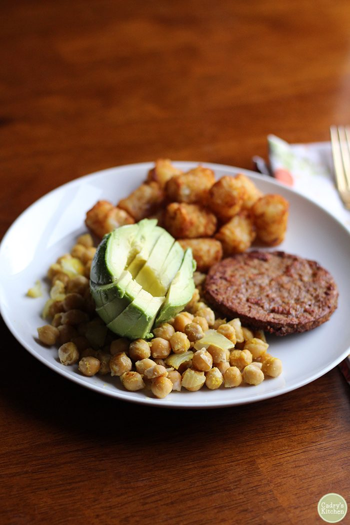 Chickpea scramble with avocado, tater tots, and breakfast sausage.