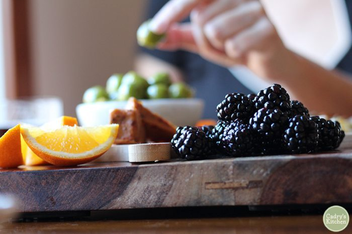 Close-up blackberries and oranges on charcuterie board.