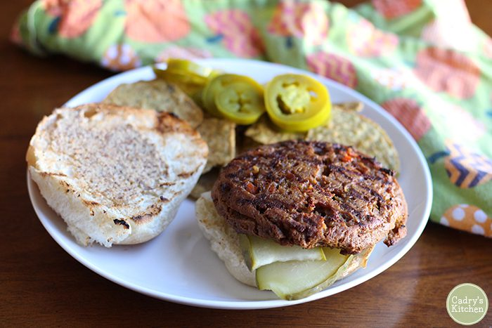 Field Roast burger on bun with jalapeno pepper slices in background.