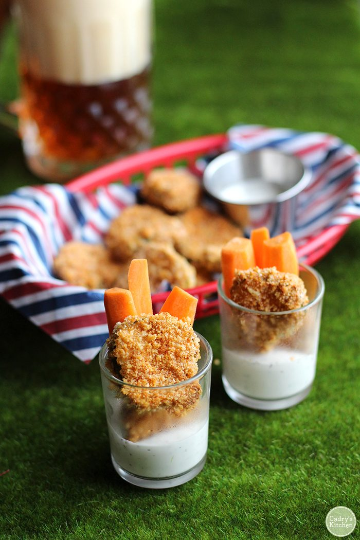 Air fried pickles in cups with vegan ranch dressing & carrots.