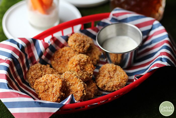 Breaded pickles in a basket with vegan ranch dressing.