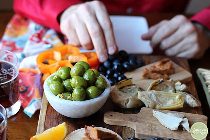 Hand reaching for blueberry on charcuterie board. Castelvetrano olives in bowl.