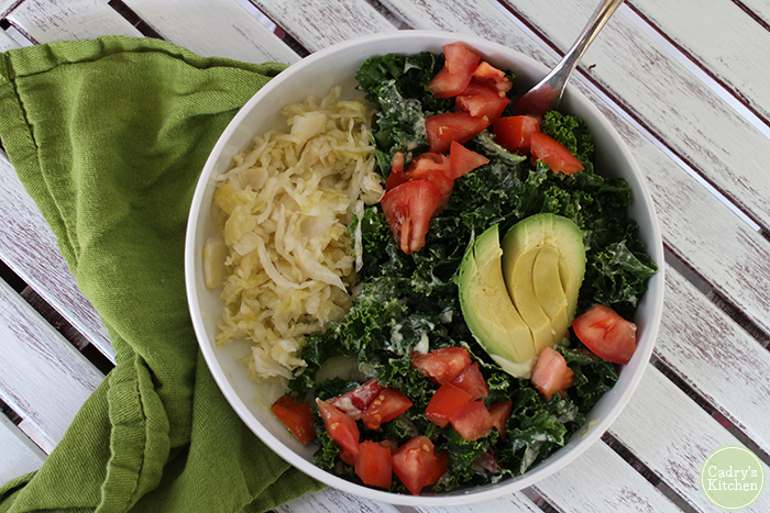 Kale salad in bowl with avocado - one of my favorite vegan sauerkraut recipes & uses.