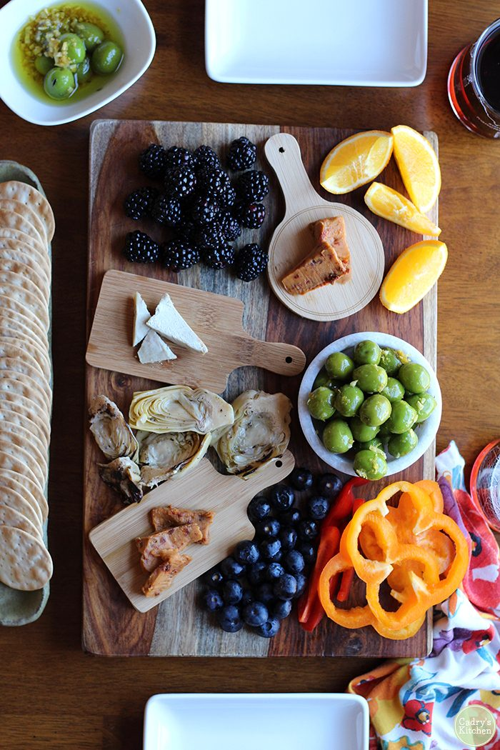 Overhead vegan charcuterie board with warmed Castelvetrano olives, crackers, non-dairy cheese, and berries.