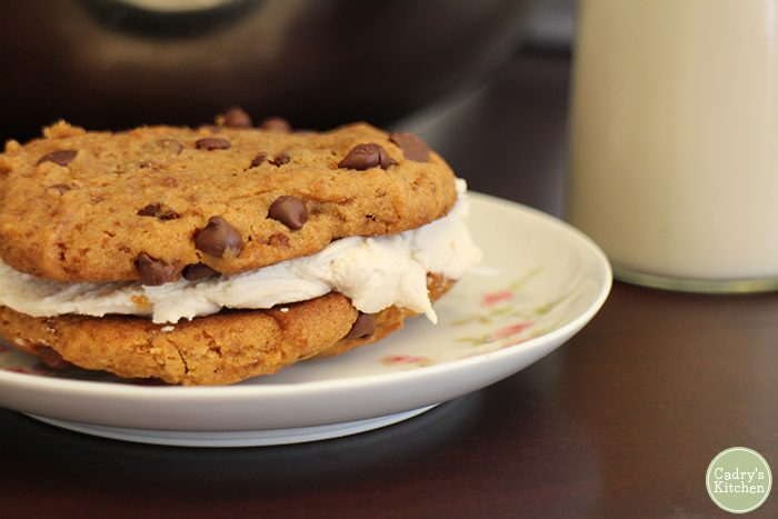 Chocolate chip cookies on plate, stuffed with vanilla frosting.
