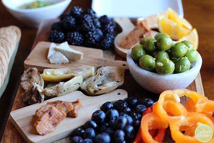 Charcuterie board with olives in bowl, non-dairy cheese, berries, and bell peppers.