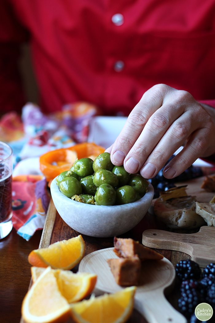 Hand reaching for warmed Castelvetrano olives in bowl.