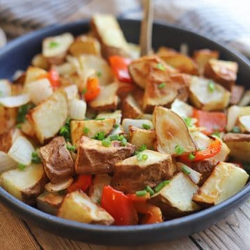 Serving bowl with potatoes, bell peppers, and onions.