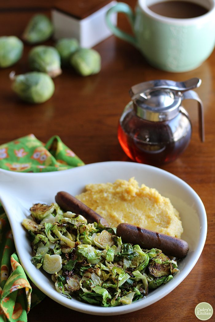 Polenta breakfast with Brussels sprouts and veggie sausage on platter next to maple syrup.