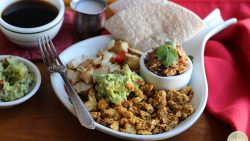 This hearty, vegan Austin breakfast is chock-full of flavor. It's packed with spicy scrambled tofu, creamy refried beans, potatoes, and guacamole. Savory breakfast lovers rejoice! | cadryskitchen.com