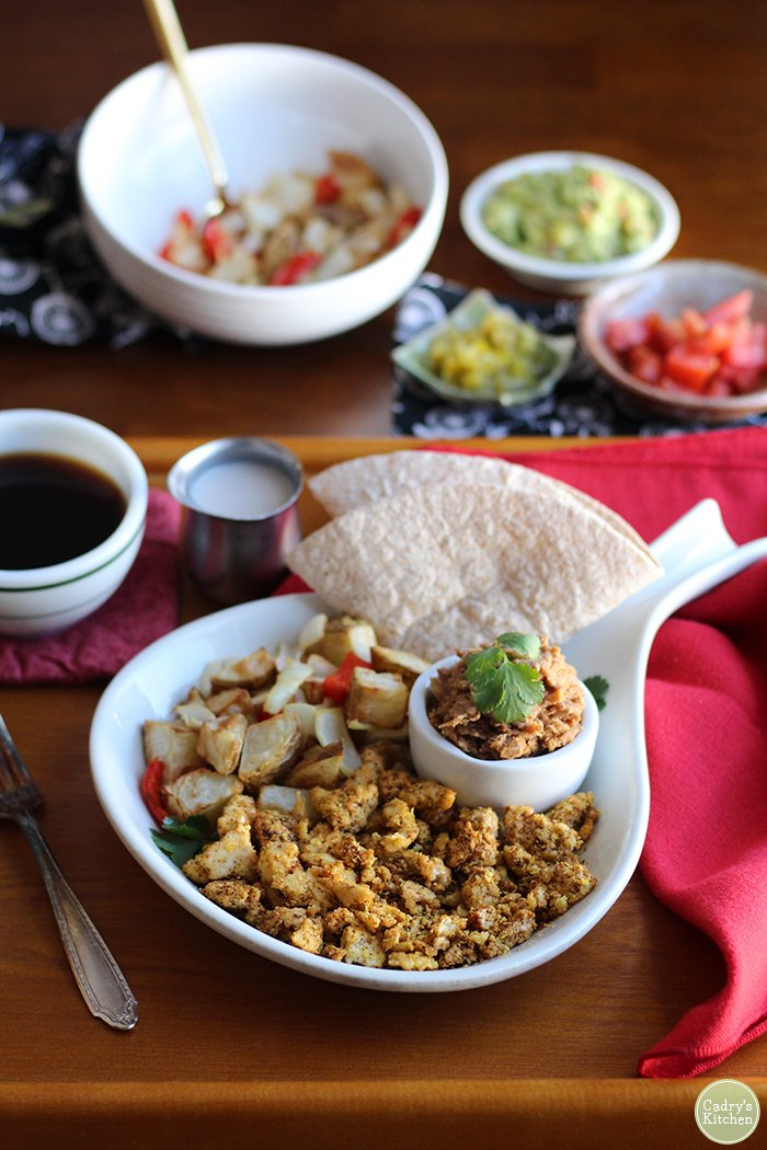 Tofu scramble on platter with roasted potatoes, refried beans, and salsa. Austin breakfast.