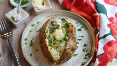 Air fryer baked potato with melting non-dairy butter and chives.