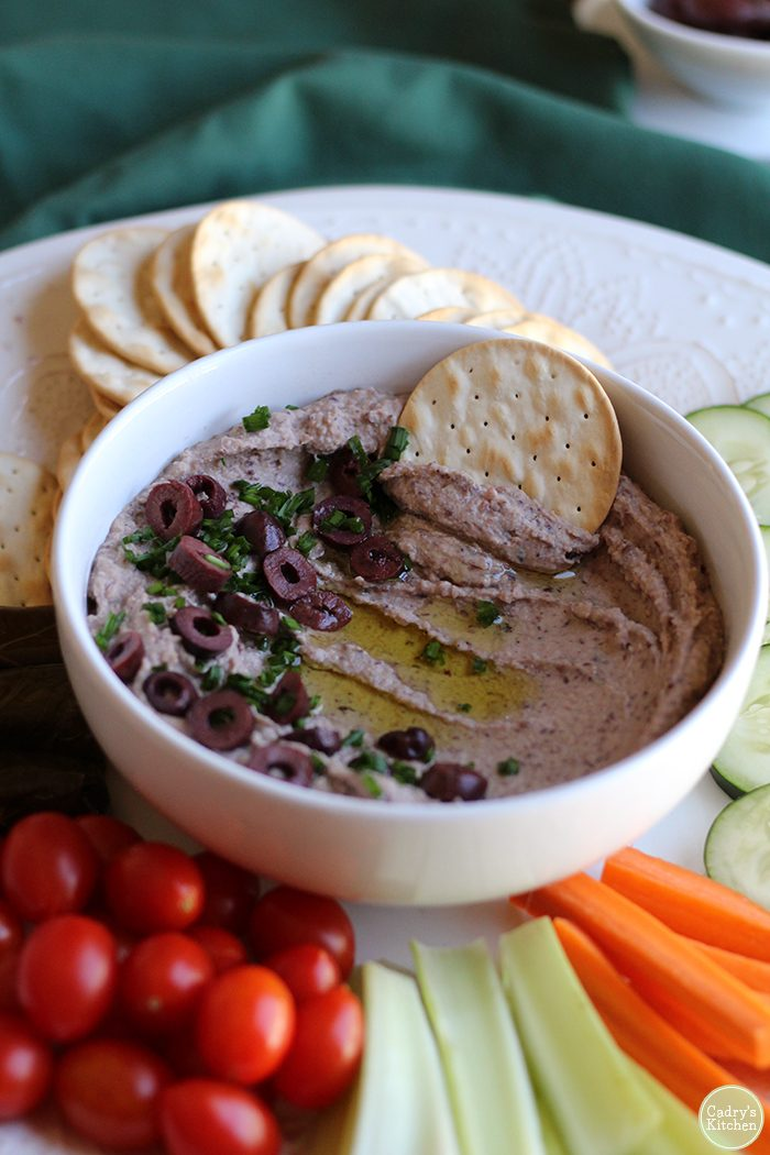 Kalamata olive hummus in bowl with cracker. Surrounded by cherry tomatoes, celery, and carrot sticks.