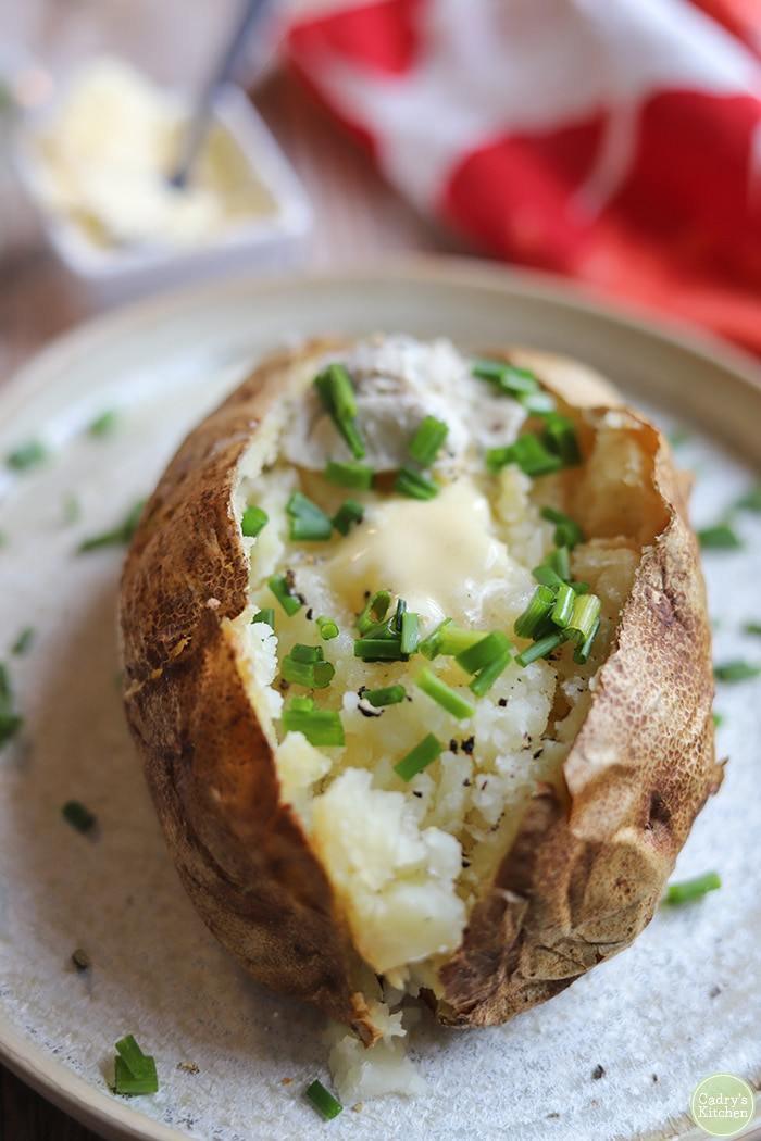 Close-up jacket potato with non-dairy butter, chives, and vegan cream cheese.