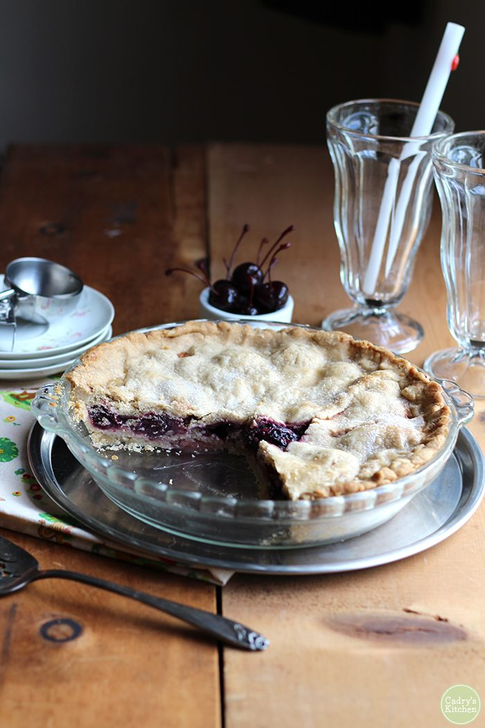 A sliced cherry pie in a baking dish with plates in the background. Two empty sundae glasses, cherries, and an ice cream scoop are in the background.