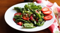 Close up picture of spinach salad with strawberries, checkered napkin, and gold fork.