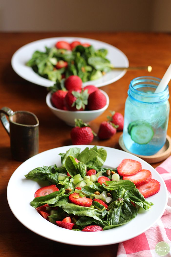 Spinach salad with a white bowl with strawberries and a little pitcher of vinaigrette.