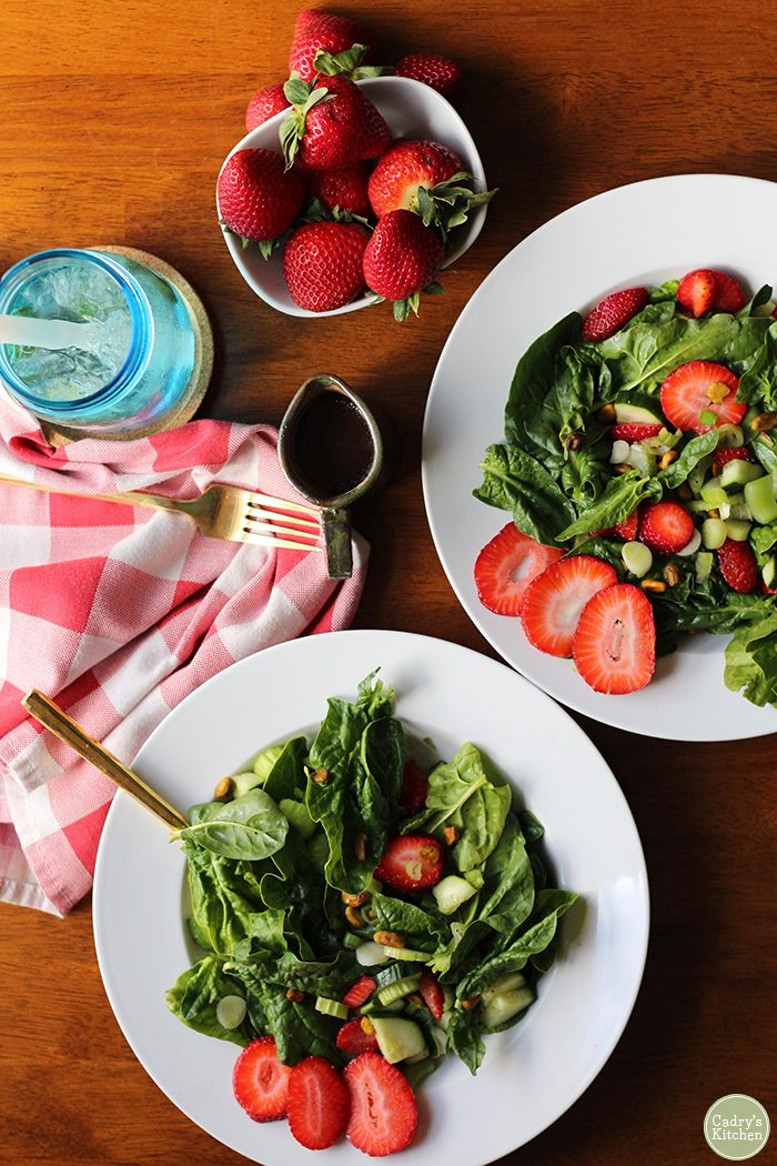 Overhead picture of two salads with spinach and strawberries, a blue water glass, and bowl of whole strawberries.
