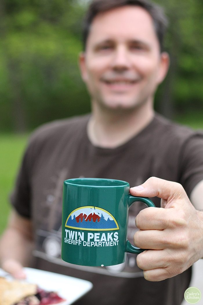 David holding a Twin Peaks mug and slice of cherry pie in the yard.