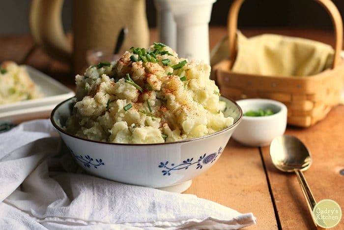 Vegan potato salad in white bowl, dotted with chives and paprika.