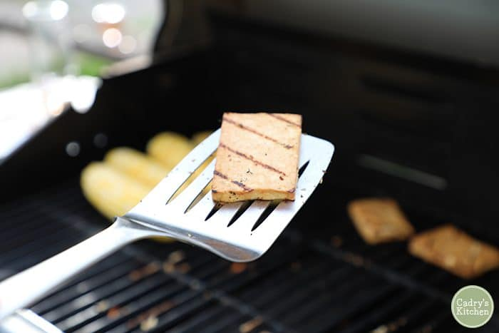 Slab of grilled lemon rosemary tofu on spatula with corn on the cob on grill in background.