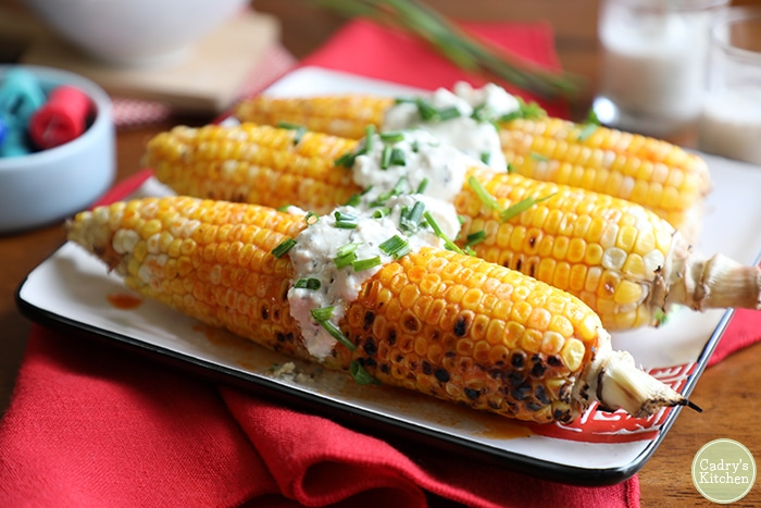 Ears of buffalo-style grilled corn on the cob topped with vegan blue cheese dressing.