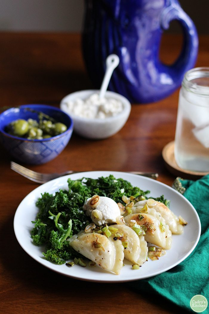 A white plate with browned pierogi, kale, and cashew cream cheese. In the background, a blue bowl with olives, blue pitcher, and white bowl of cashew cream cheese.