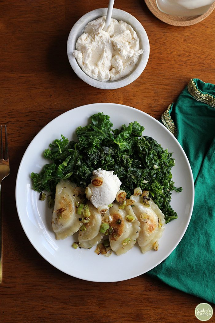 Overhead shot of browned kale on plate with pile of kale, and dollop of cashew cream cheese. A green napkin on the side.
