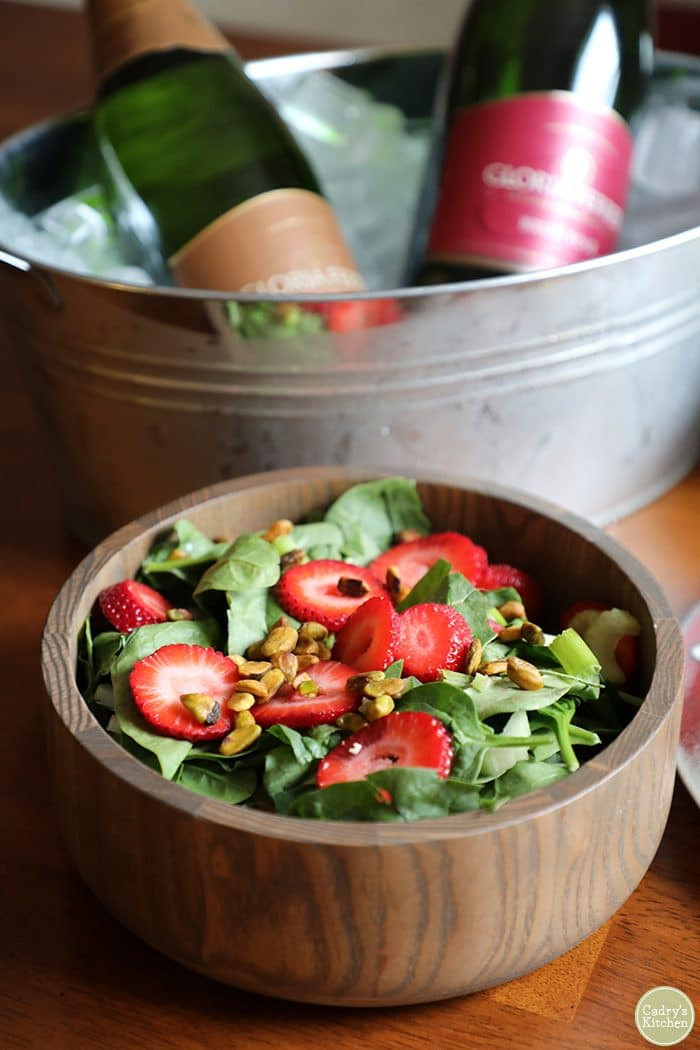 Strawberry spinach salad in wood bowl with pistachios.