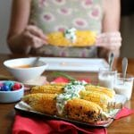 Buffalo corn on the cob with a vegan blue cheese topping on a red napkin. Cadry in background holding ear of corn.