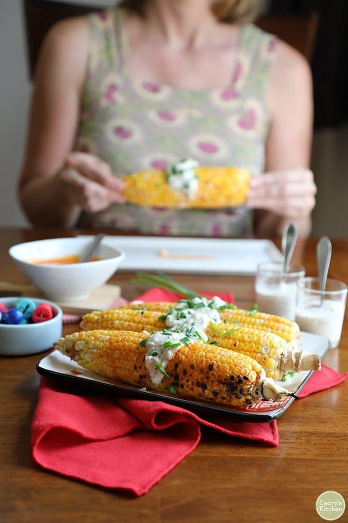 Buffalo-style grilled corn on the cob with a vegan blue cheese topping on a red napkin. Cadry in background holding ear of corn.
