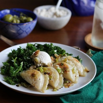 Browned pierogi on a white plate with kale & cashew cream cheese. In the background, a green napkin, water glass, blue bowl, and olives.