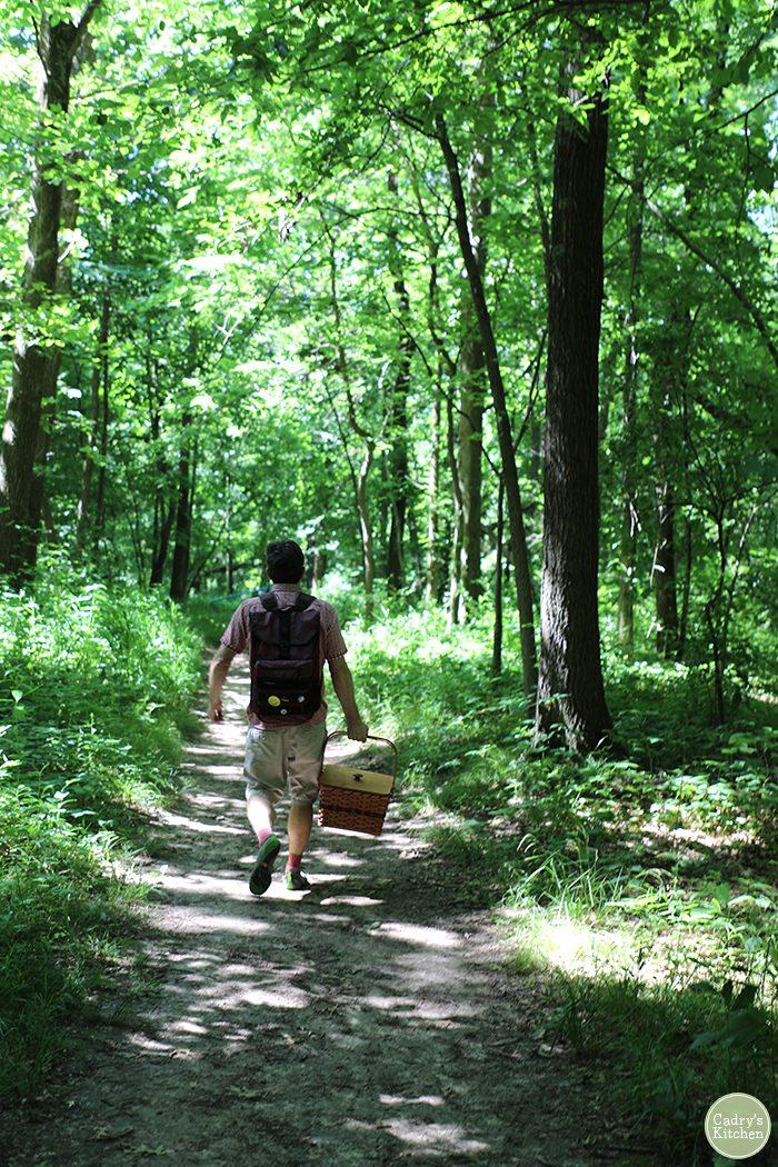 David carrying picnic basket, walking path through trees.