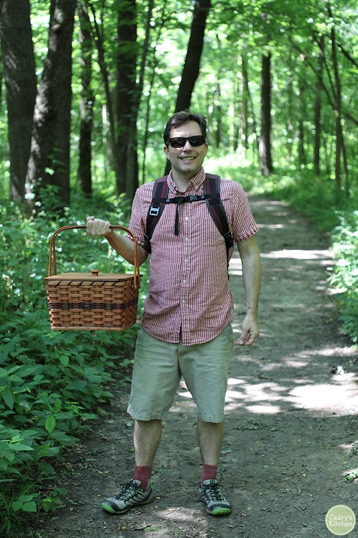 David carrying picnic basket through trees on path.