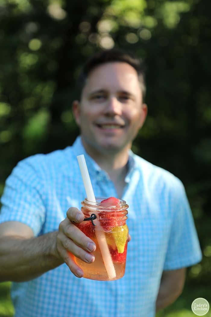David holding sparkling strawberry lemonade in a jar with white straw.