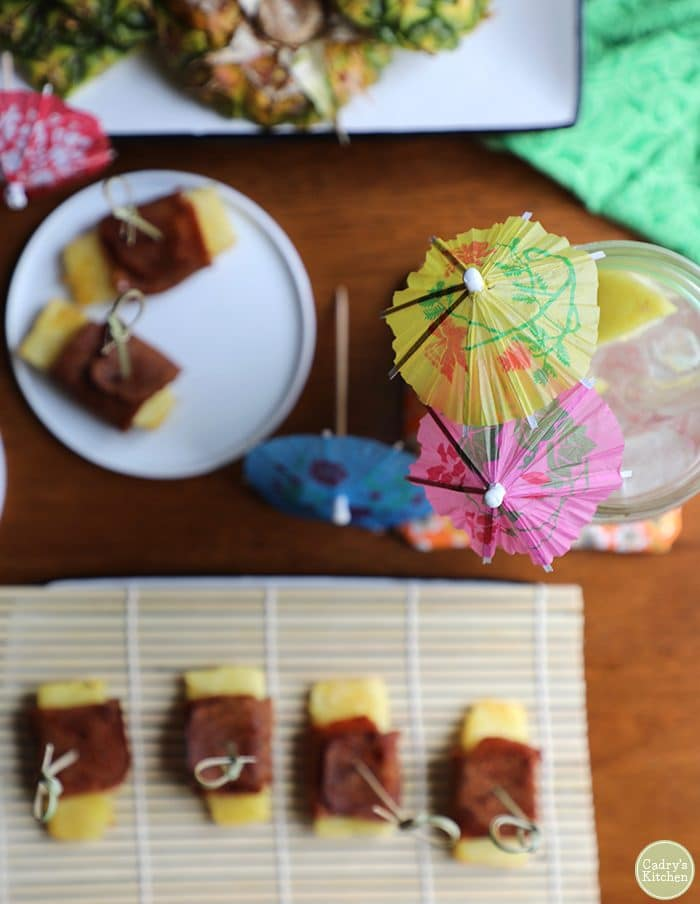 Overhead cocktail parasols & seitan bacon wrapped pineapple with bamboo skewers.