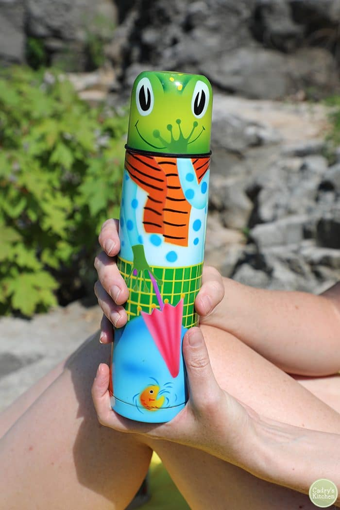 Hands holding frog thermos.